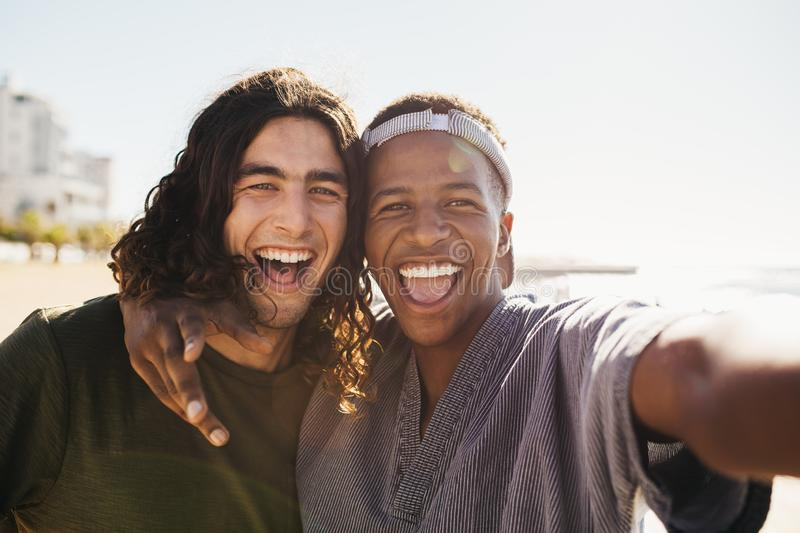 Cheerful friends making a selfie outdoors. Two mixed race male friends taking selfie outside on a summer day. Cheerful friends making a selfie outdoors stock photo