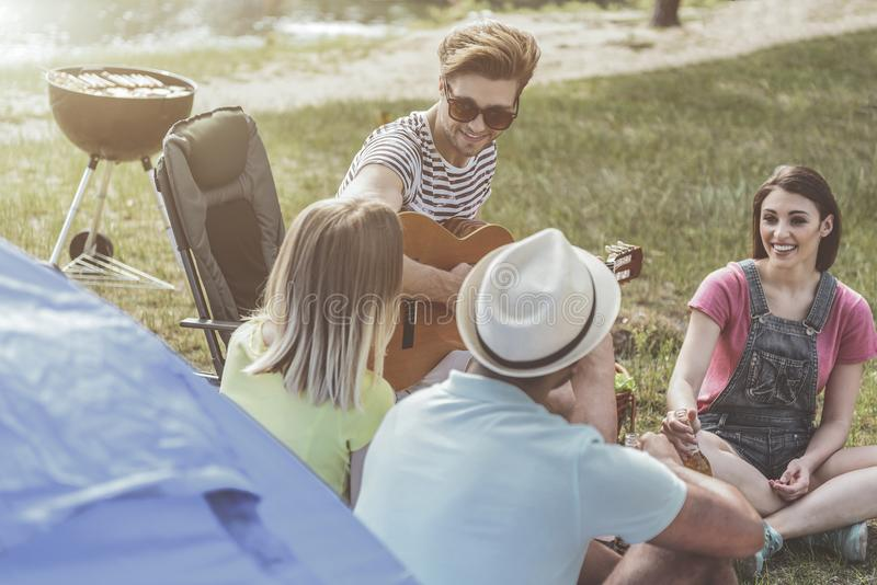 Cheerful friends organizing picnic with a song. Wonderful holiday. Young company sitting near tent and grill. They are holding beer and enjoying their mate stock photo