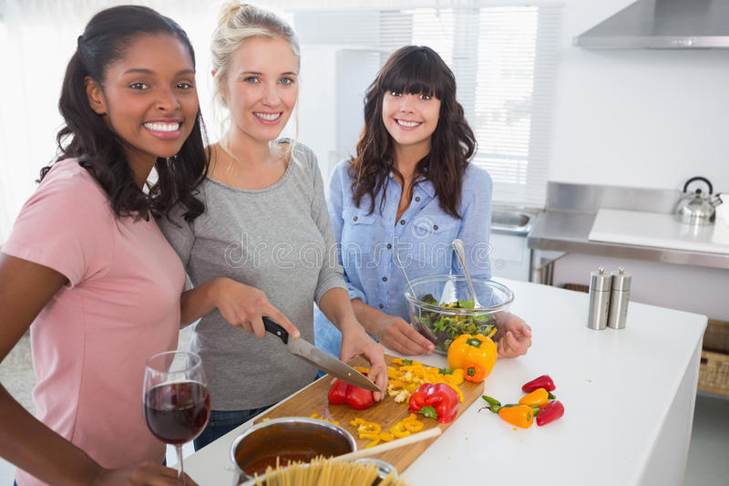 Cheerful friends preparing a meal together looking at camera royalty free stock photography