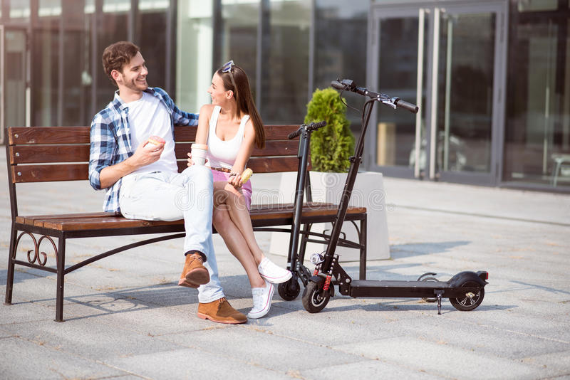 Cheerful friends resting on the bench stock images