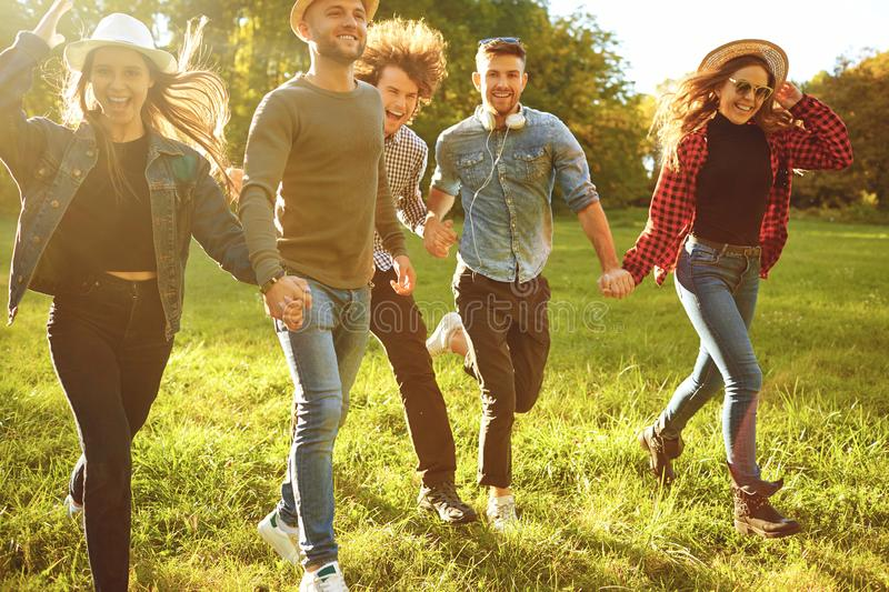 Cheerful friends are running in the park. stock image