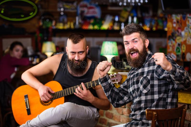 Cheerful friends sing song guitar music. Relaxation in pub. Friends relaxing in pub. Live music concert. Man play guitar. In pub. Acoustic performance in pub royalty free stock photos