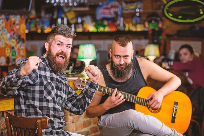 Cheerful friends sing song guitar music. Relaxation in pub. Friends relaxing in pub. Live music concert. Man play guitar. In pub royalty free stock images