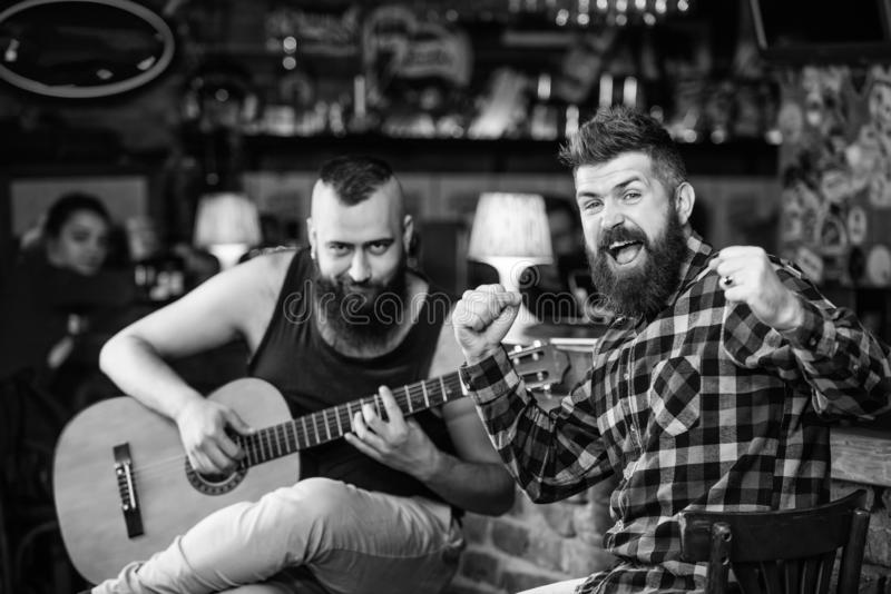 Cheerful friends sing song guitar music. Relaxation in pub. Friends relaxing in pub. Live music concert. Man play guitar. In pub stock images