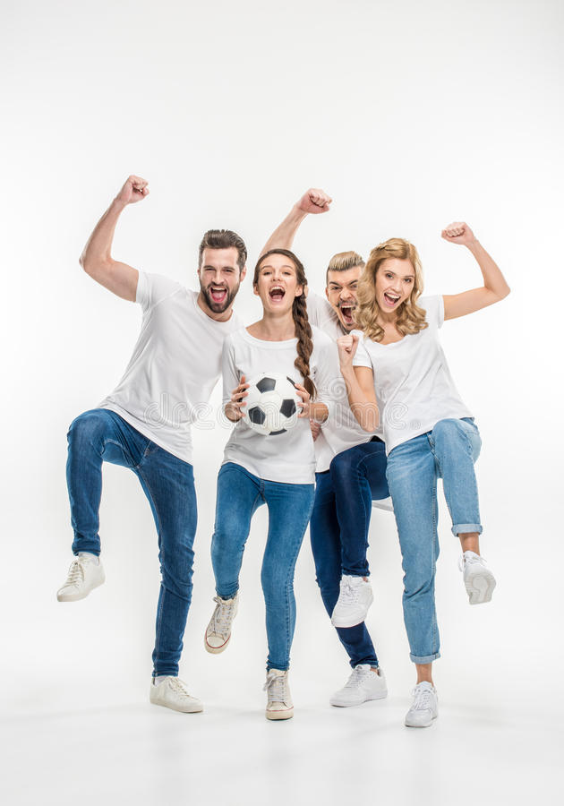 Cheerful friends with soccer ball. Cheerful young friends with soccer ball and raised hands looking at camera on white royalty free stock images