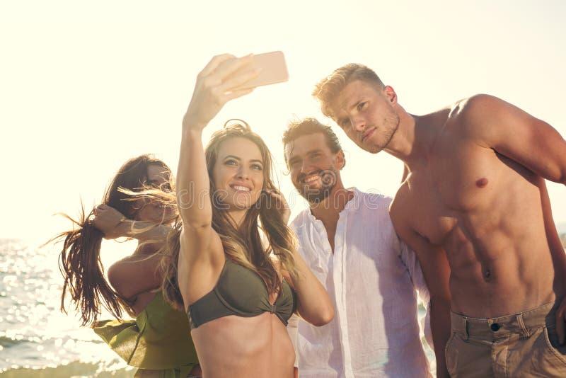 Cheerful friends taking selfie at beach stock photos