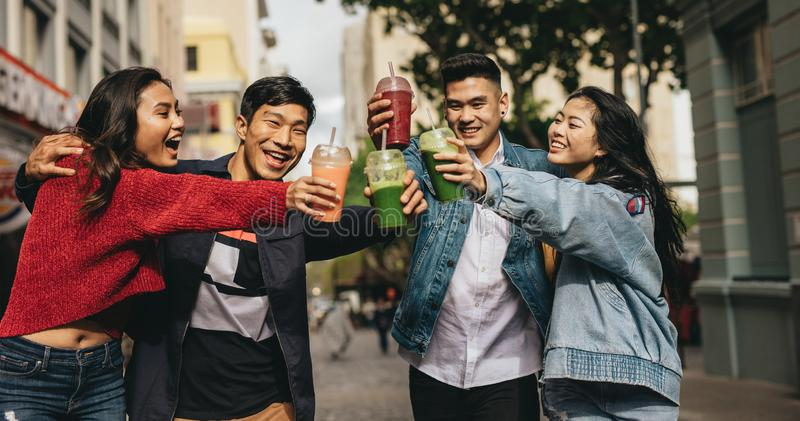 Cheerful friends toasting drinks on the street royalty free stock photos