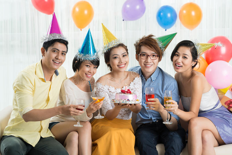 Cheerful friends. Toasting and looking at the camera at the birthday party stock image