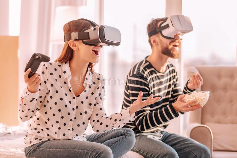 Cheerful friends watching an exciting film at home. Come on. Cheerful nice friends watching an exciting film using virtual reality glasses at home royalty free stock images