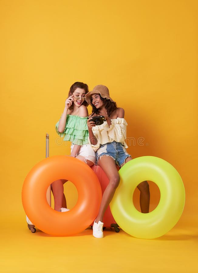 Cheerful friends woman dressed in summer clothes sitting on a suitcase and rubber ring isolated over yellow background. Cheerful friends women dressed in summer stock image