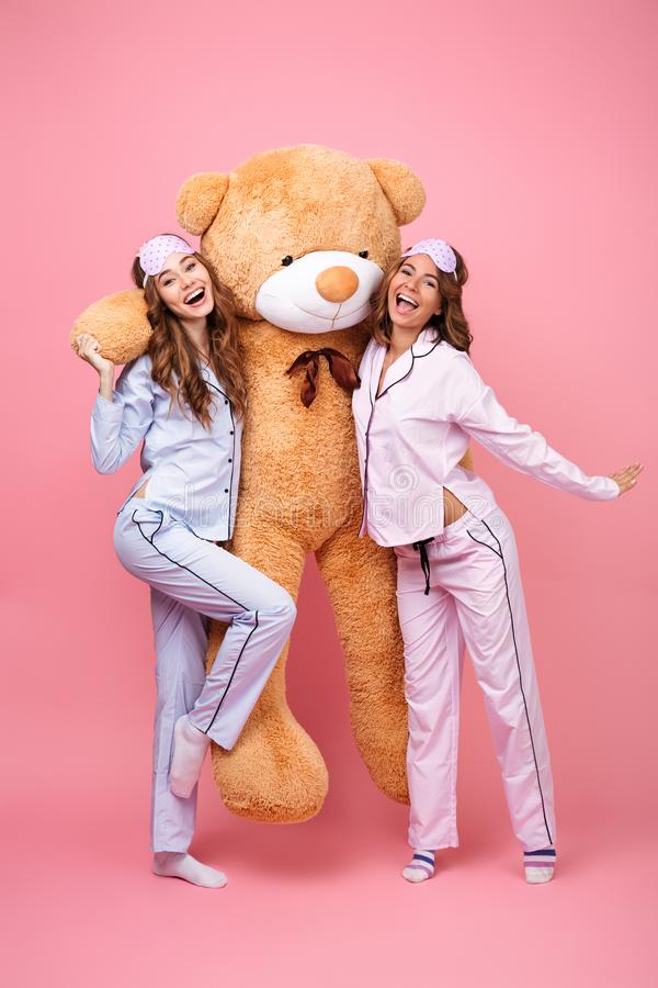 Cheerful friends women in pajamas hug big teddy toy bear. Picture of two cheerful friends women in pajamas isolated over pink background hug big teddy toy bear stock photography