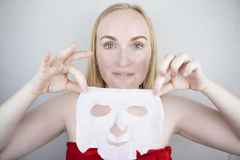 Cheerful and funny girl fooling around and grimacing in a moisturizing face mask. Morning beauty treatments, oily and. A cheerful and funny girl fooling around royalty free stock images