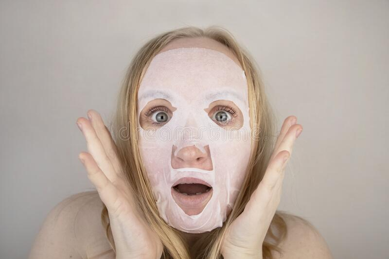 Cheerful and funny girl fooling around and grimacing in a moisturizing face mask. Morning beauty treatments, oily and. A cheerful and funny girl fooling around stock image