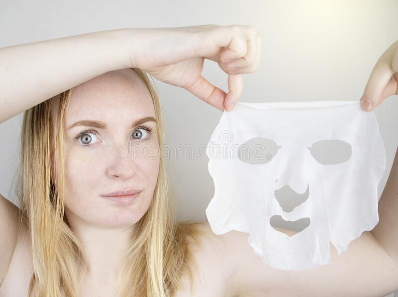 Cheerful and funny girl fooling around and grimacing in a moisturizing face mask. Morning beauty treatments, oily and. A cheerful and funny girl fooling around royalty free stock photo
