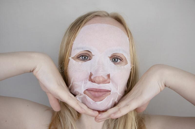 Cheerful and funny girl fooling around and grimacing in a moisturizing face mask. Morning beauty treatments, oily and. A cheerful and funny girl fooling around royalty free stock photography
