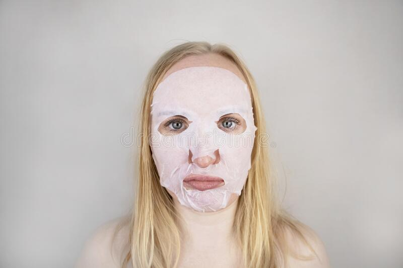 Cheerful and funny girl fooling around and grimacing in a moisturizing face mask. Morning beauty treatments, oily and. A cheerful and funny girl fooling around stock photo