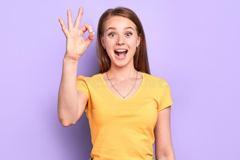 Cheerful funny girl showing okay gesture, saying good job or well done. Optimistic and positive feelings, happy face expression with wide eyes and mouth opened royalty free stock photography