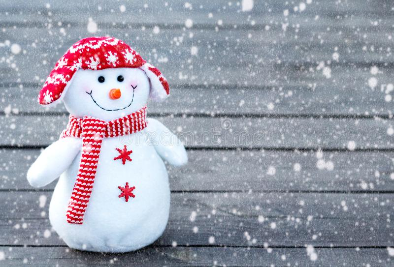 Cheerful and funny snowman in a red hat and red scarf on a gray wooden background. falling snow texture royalty free stock images