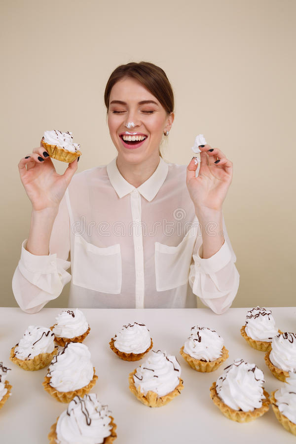 Cheerful funny young woman eating cakes and laughing. Over white background stock photo