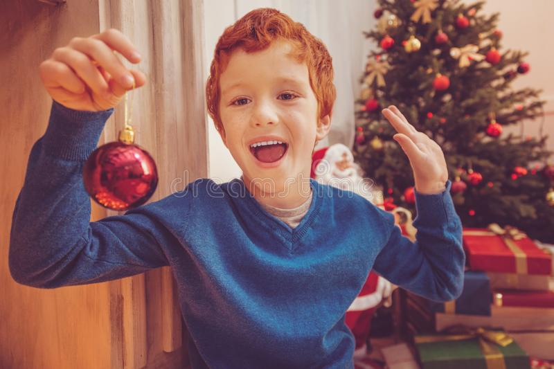 Cheerful ginger-haired boy showing new Christmas bauble royalty free stock photo