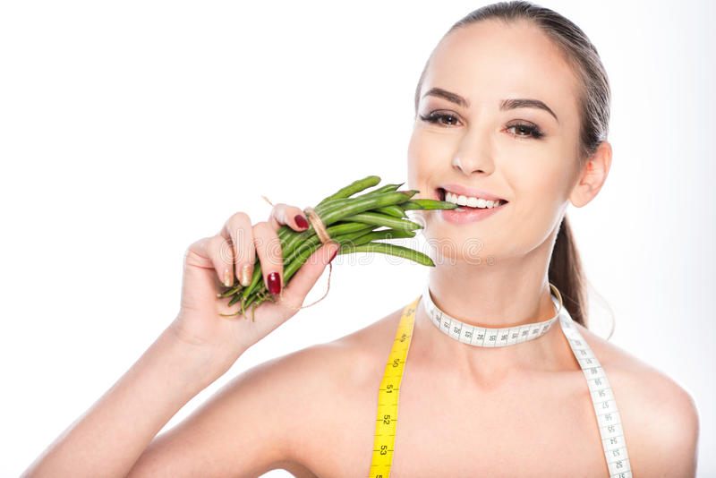 Cheerful girl biting green beans royalty free stock photography