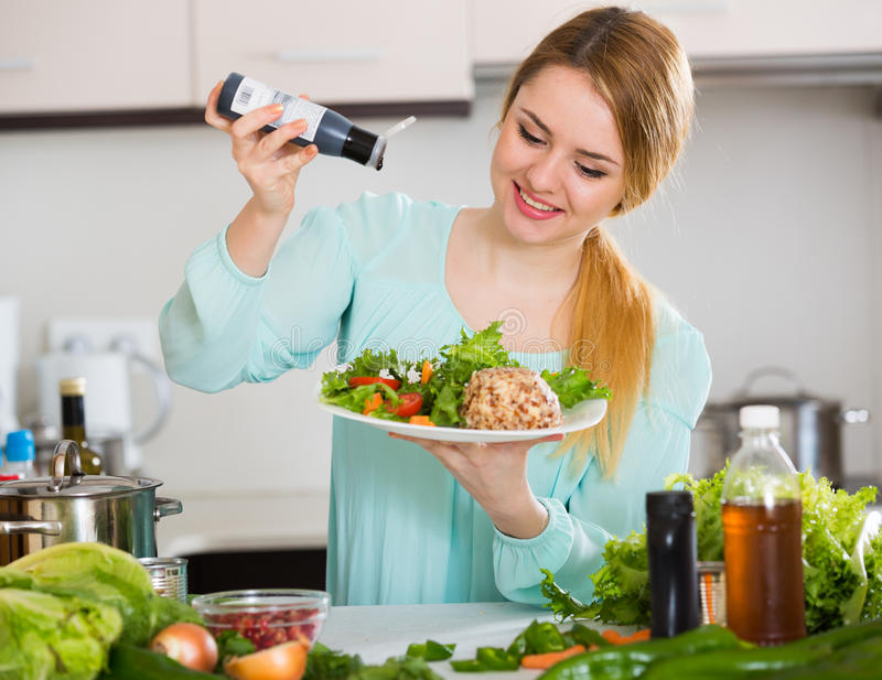Cheerful girl in blouse adding sauce in salad with cheese. Young woman with vegetable salad and balsamic vinegar indoors royalty free stock images