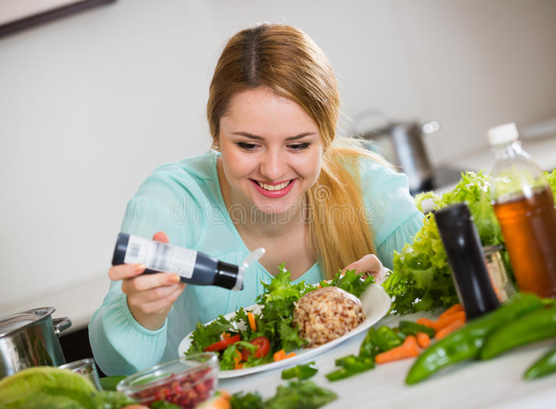 Cheerful girl in blouse adding sauce in salad with cheese. Young woman with vegetable salad and balsamic vinegar indoors stock photos