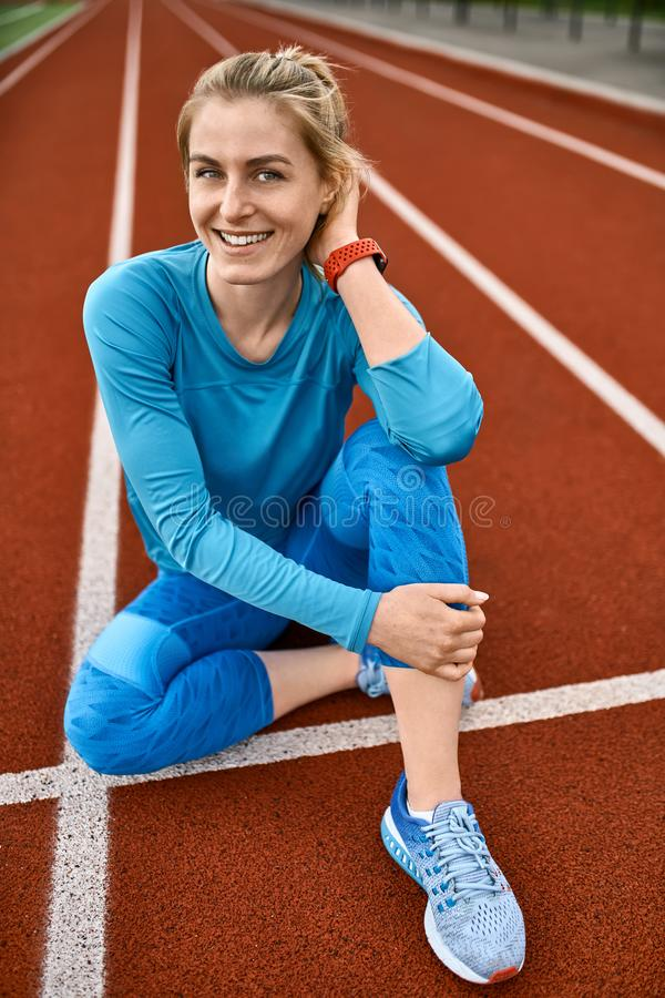 Sportive blonde woman posing at open stadium royalty free stock images
