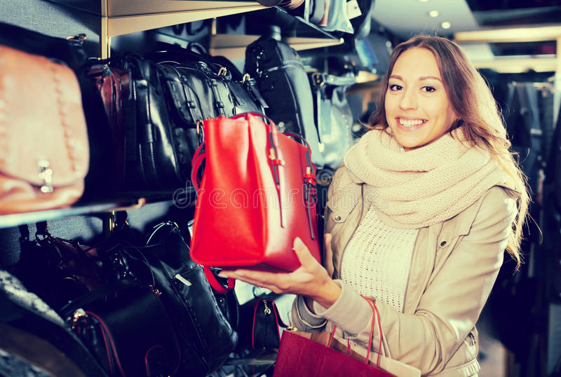 Download Cheerful Girl Choosing Bag Among Assortment Stock Photo - Image: 83702794