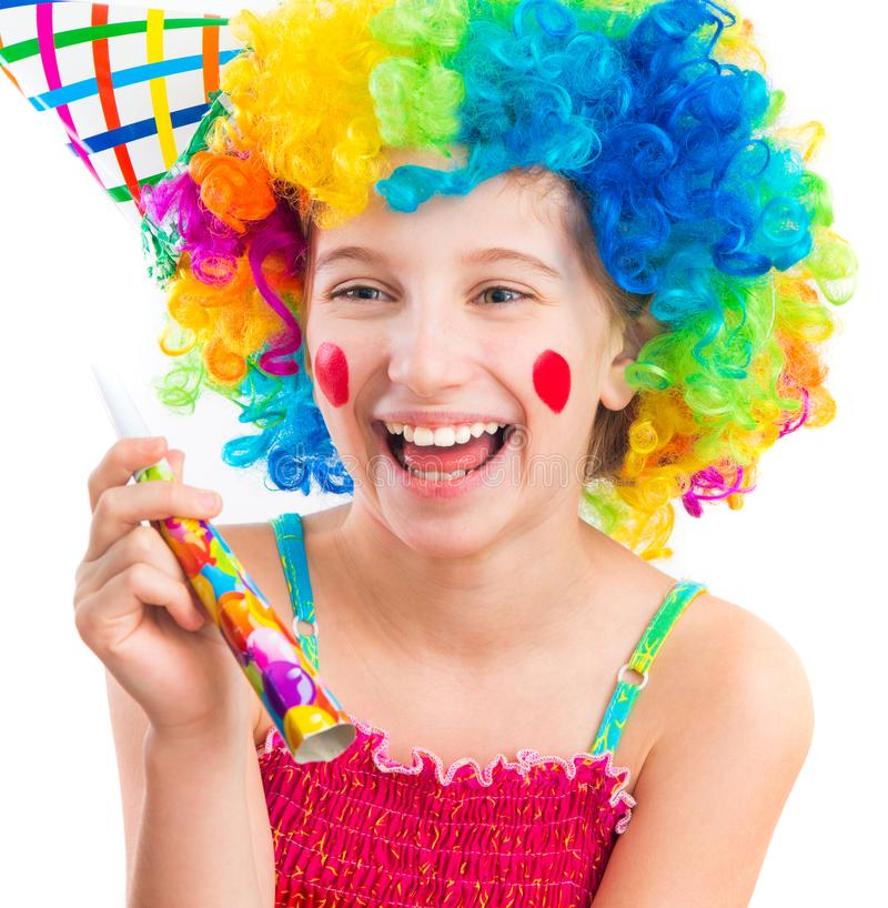 Cheerful girl in curly clown wig and party horn blower stock image