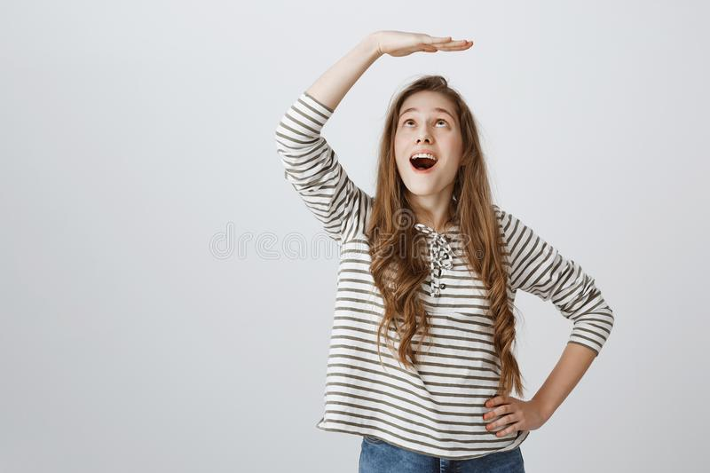 Cheerful girl dreams to become higher. Portrait of attractive playful woman raising palm above head as if measuring stock images