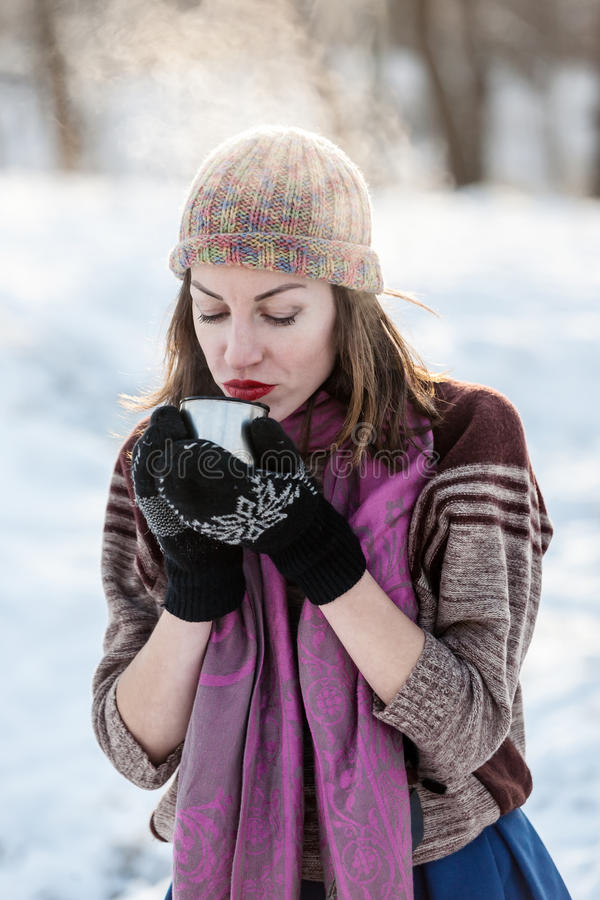 Cheerful girl drinking hot tea with steam outdoor. stock photography