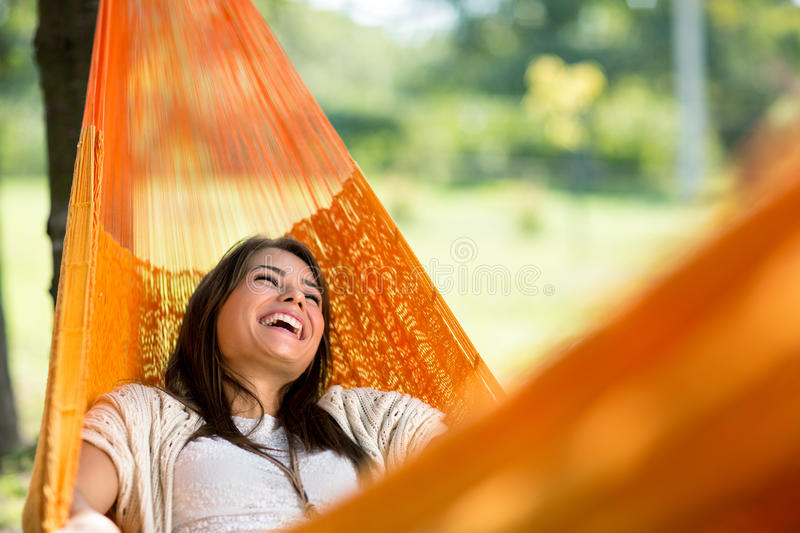 Cheerful girl enjoy in hammock. Cheerful girl enjoy in orange hammock outdoor royalty free stock photos