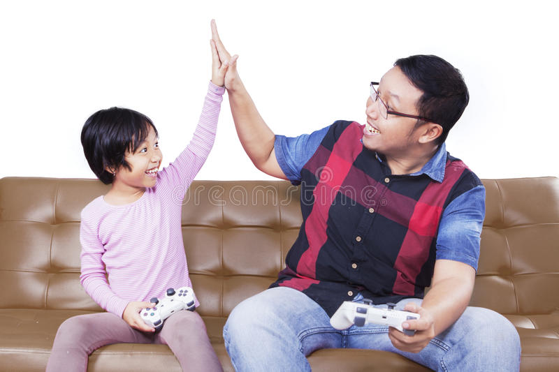 Cheerful girl and father playing video games stock image