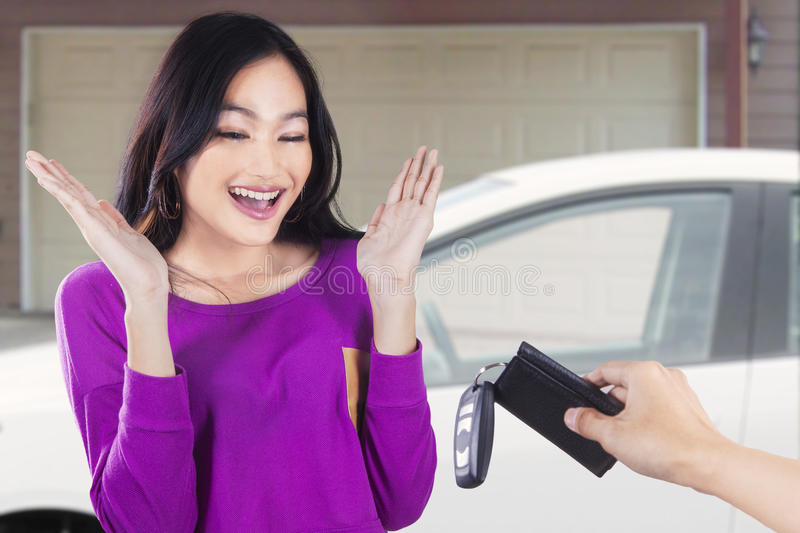 Cheerful girl get new car at garage royalty free stock photo