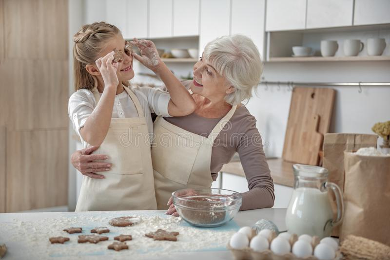 Carefree child enjoying baking process with her grandmother stock photography