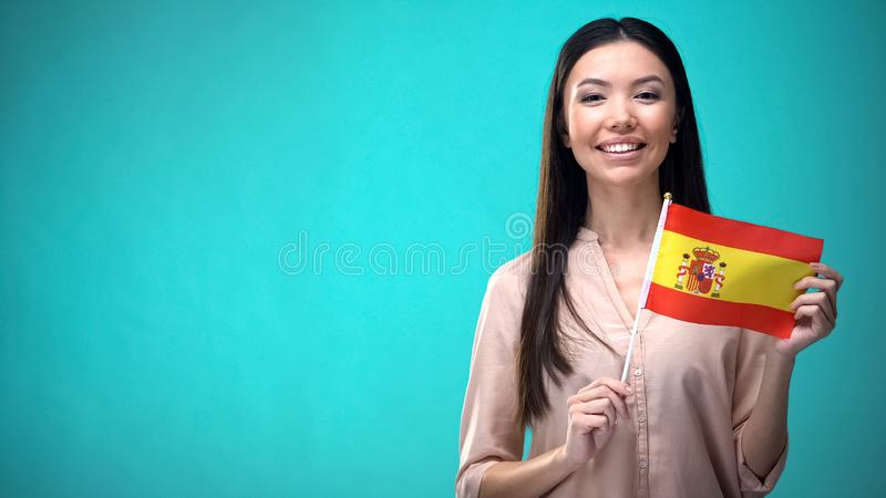 Cheerful girl holding Spain flag ready to learn foreign language, Spanish school. Stock photo royalty free stock photos