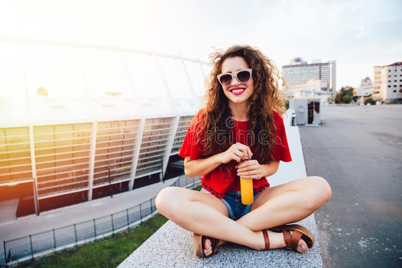 Cheerful girl holds a bottle with drink while sitting on marble slab royalty free stock photo