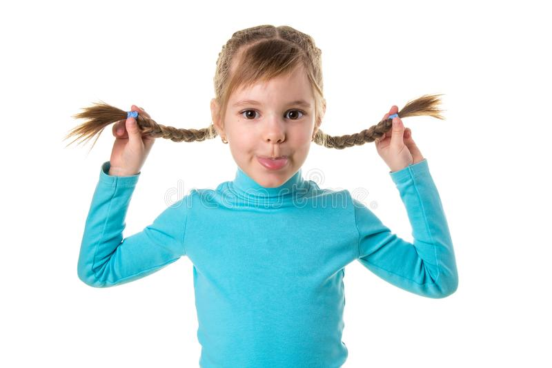 Cheerful girl making funny face. Funny little girl isolated on white background. Beautiful caucasian model with two. Braids holding them up royalty free stock photo