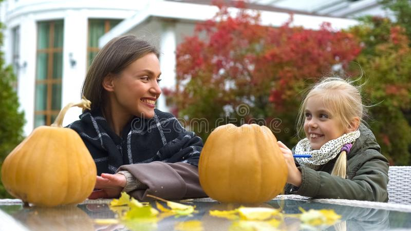 Cheerful girl and mom painting scary face on pumpkin, spend time together, fun stock photo