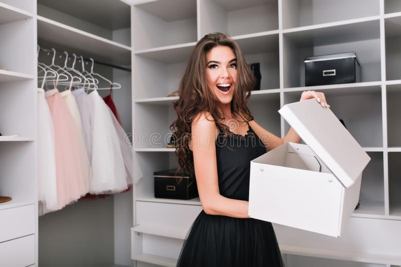 Cheerful girl in nice wardrobe holding box with shoes royalty free stock images