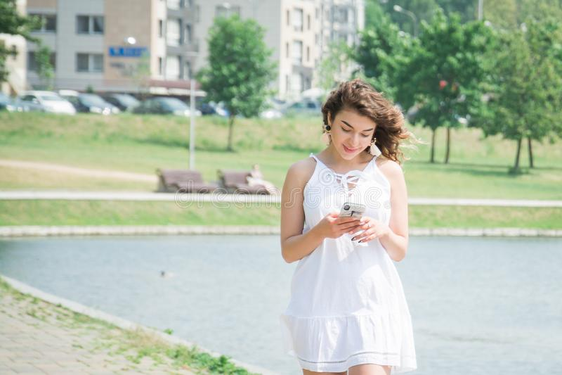 Cheerful girl in the park types sms and walks. On a summer day stock image