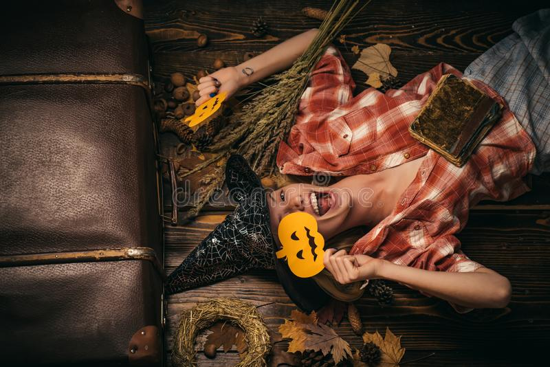 Cheerful girl play with pumpkins. Funny woman in carnival costumes on wood background. Smiling girl having fun at stock photography