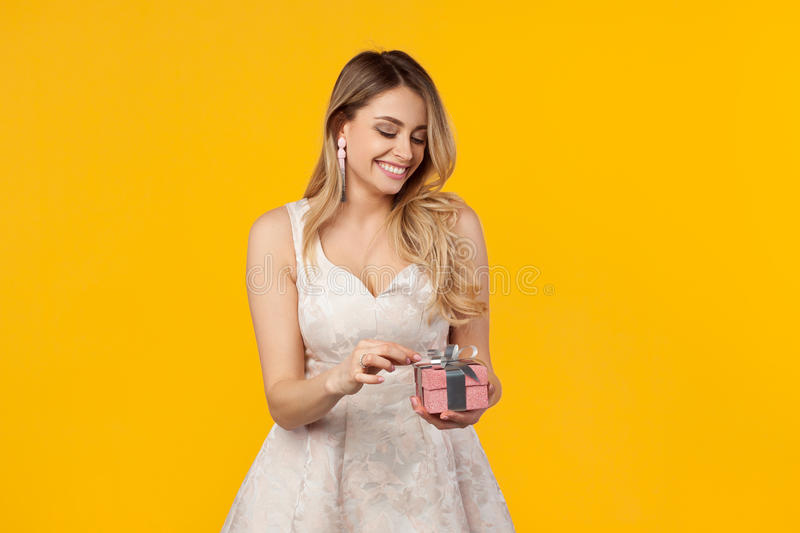 Cheerful girl with present on yellow stock photo