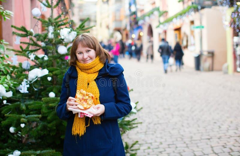 Cheerful girl with pretzel on Christmas market stock photo