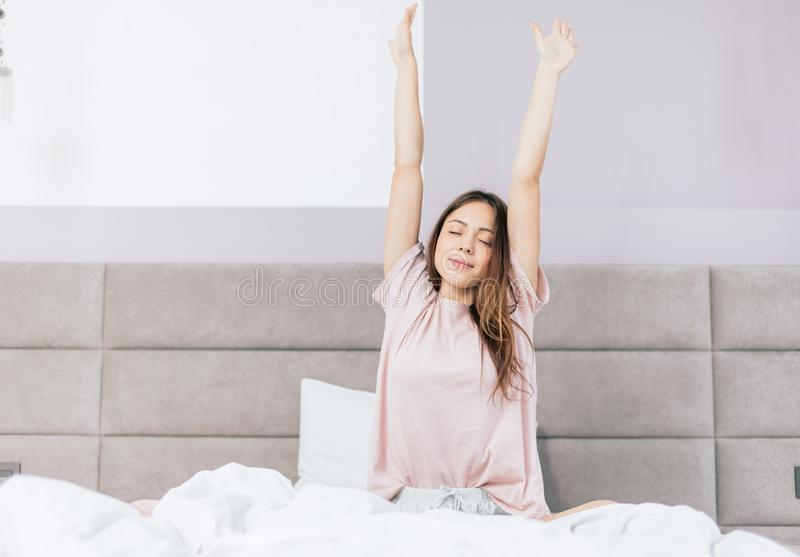 Cheerful girl with raised arms waking up stock images