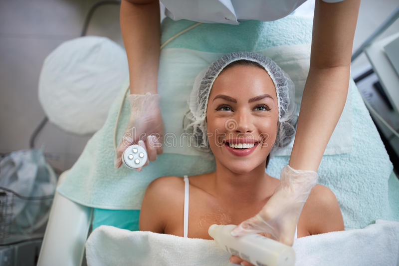 Cheerful girl is receiving facial treatment by beautician royalty free stock photos