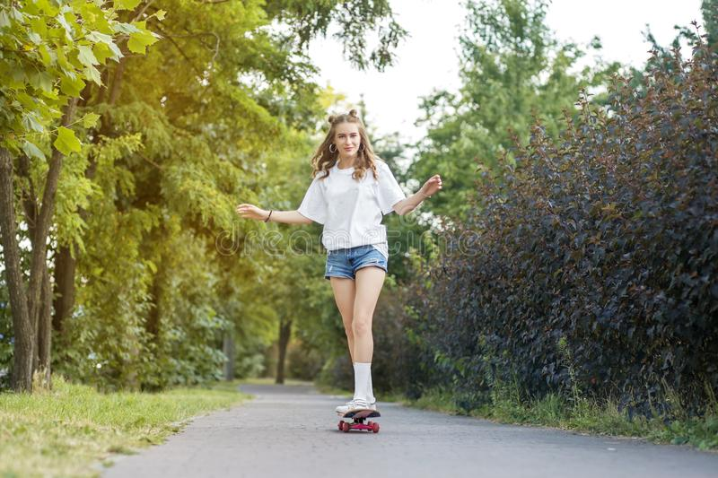 Cheerful girl rides a skate board in the park. The concept of lifestyle, leisure stock images