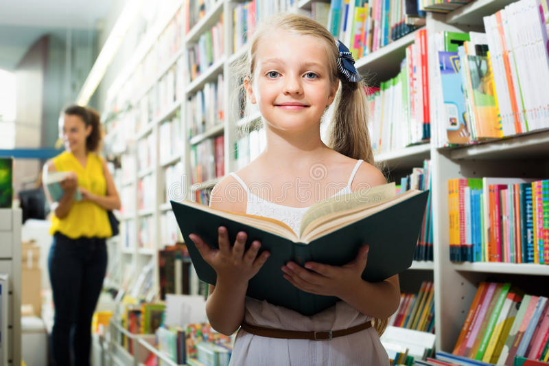 Cheerful girl in school age taking chosen book. In bookstore stock images
