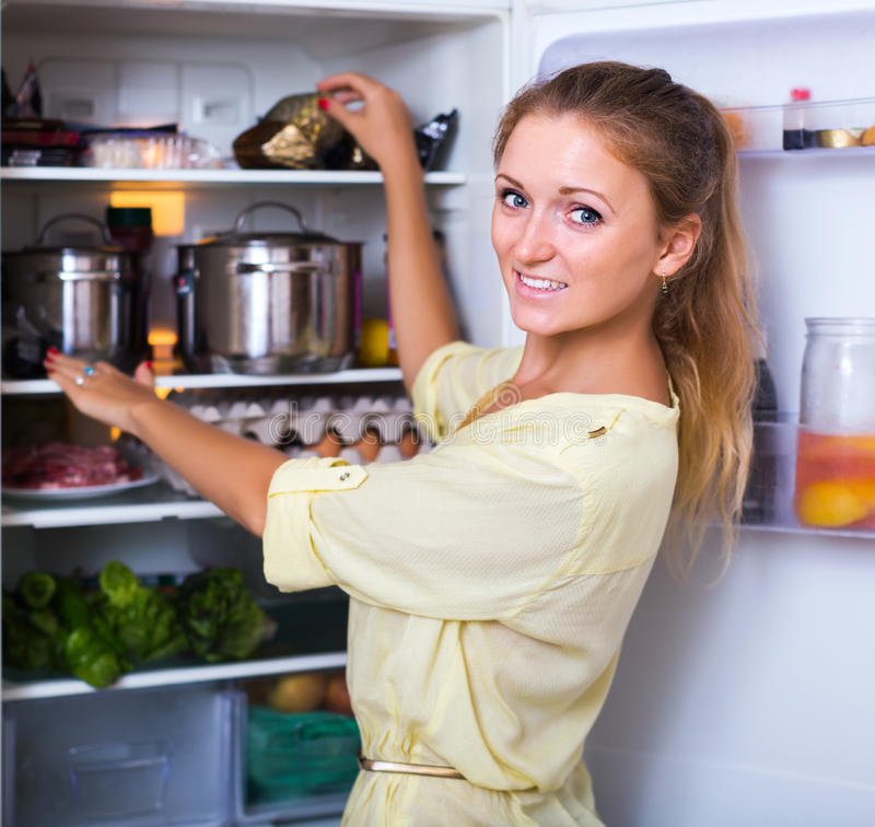 Cheerful girl searching in refrigerator stock photography